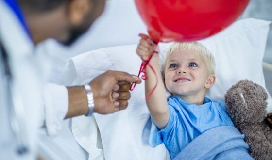 Young boy in hospital bed holding a balloon