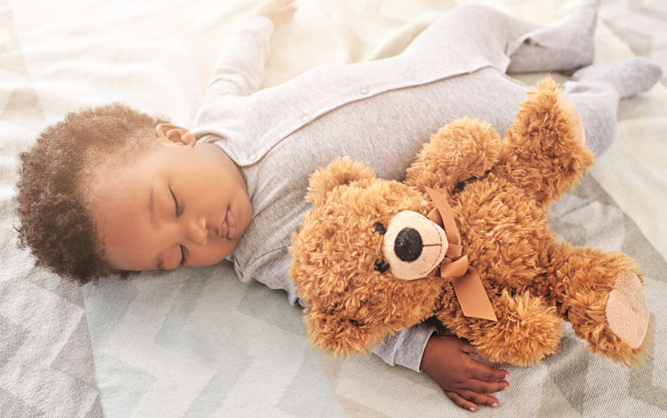 Infant sleeping with stuffed bear